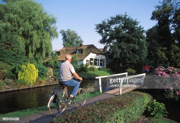 Cycliste au bord d'un canal du village lacustre de Giethoorn, Pays-Bas.