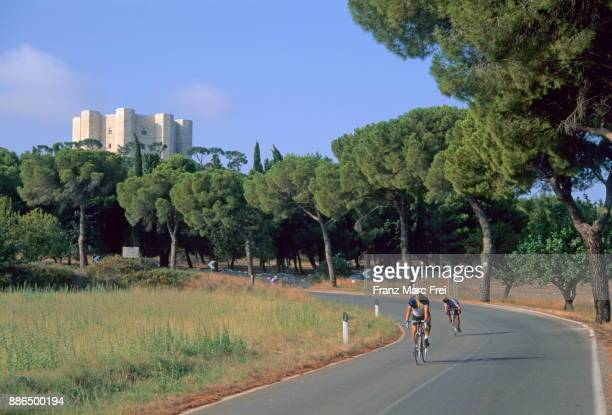 Cyclists and Castel del Monte in the background, Andria, Apulia, Italy