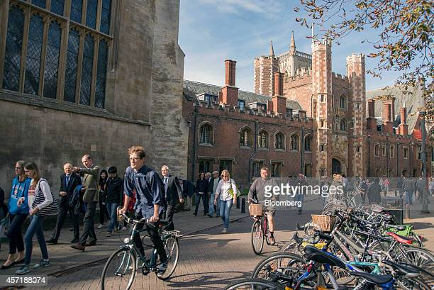 Cyclists and pedestrians move along Trinity Street past St Johns College part of the University of Cambridge in Cambridge UK on Sunday Oct 5 2014 As...