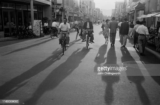 Cyclists and pedestrians on a street in Hiroshima, Japan, 1955. Original Publication : Picture Post - 7849 - Hiroshima - pub. 6th August 1955.