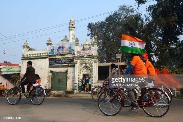 Cyclists bearing flags with the Hindu 'Om' symbol and the Indian tricolour ride past a mosque during the 26th anniversary of the demolition of the...