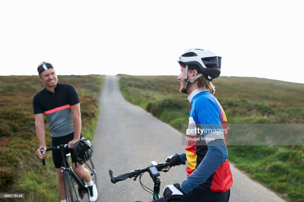 Cyclists chat and laugh on small road in the countryside.