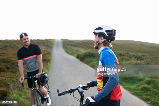 Cyclists chatting on road in countryside.