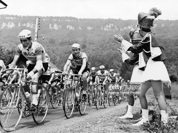 Cyclists competing in the Tour de France bicycle race ride in a pack as several drum majorettes in uniform clap and cheer them on on the...