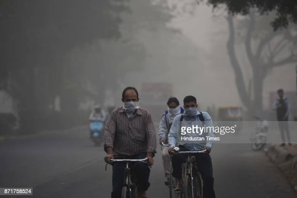 Cyclists cover their faces to avoid pollution amid heavy smog on November 8 2017 in New Delhi India Delhi was enveloped in a thick blanket of haze...