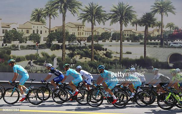 Cyclists cycle past an advertisement billboard during the second stage of Dubai Tour 2016 in Dubai on February 4 2016 Italy's Elia Viviani riding for...