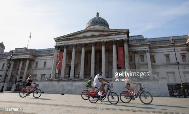 Cyclists cycle past The National Gallery in Trafalgar Square on June 23, 2020 in London, United Kingdom.