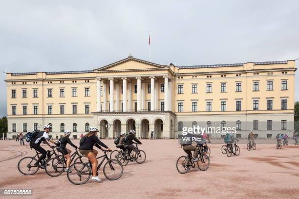 Cyclists cycling past the Royal Palace Det Kongelige Slott Oslo Norway