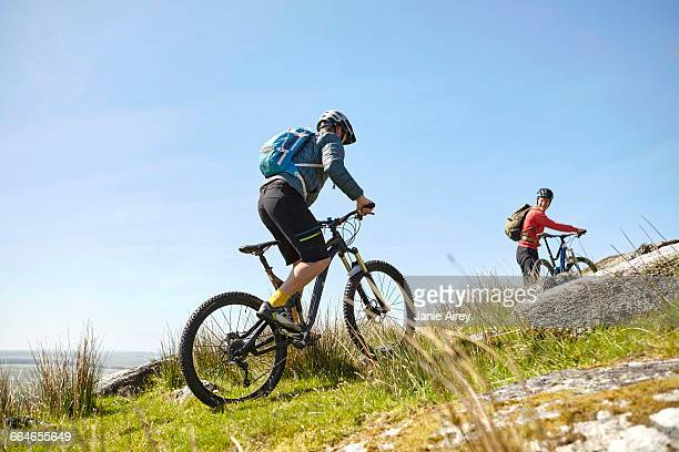 Cyclists cycling up hillside