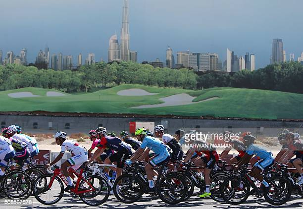 Cyclists drive past an advertisment billboard as they compete in the third stage of the Tour of Dubai at the steep Hatta Dam way east of the Gulf...