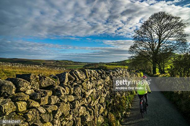 cyclists explore the yorkshire dales in november - stone wall stock pictures, royalty-free photos & images