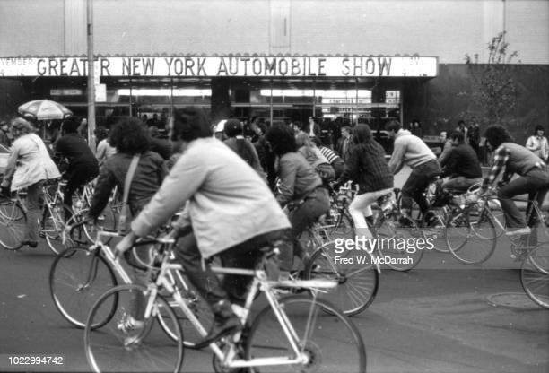 Cyclists from Action Against Automobiles ride their bicycles past the entrance to Greater New York Automobile Show held at the Coliseum New York New...