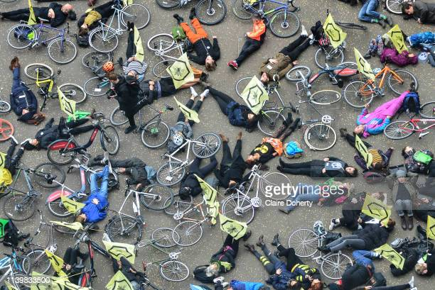 Cyclists from Extinction Rebellion flying golden bee flags from their backpacks stage a die in demonstration at Tate Modern called XR Critical Swarm...