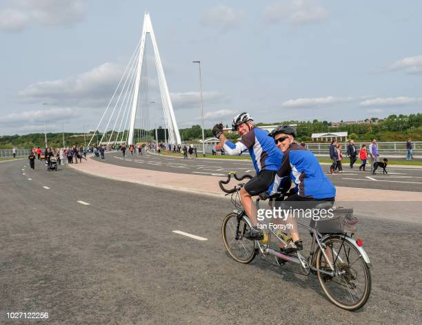 Cyclists gesture as they ride across the new Northern Spire bridge spanning the River Wear as it opens for a pedestrian walkover on August 28 2018 in...