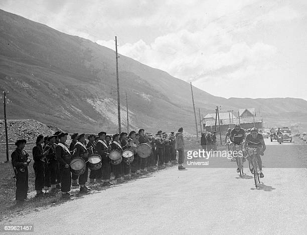 Cyclists Gino Bartali and Fausto Coppi pass a marching band They are leading the pack in the 17th stage of the 1949 Tour de France The area in which...