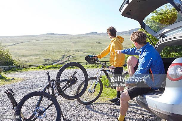 Cyclists holding bicycles by car