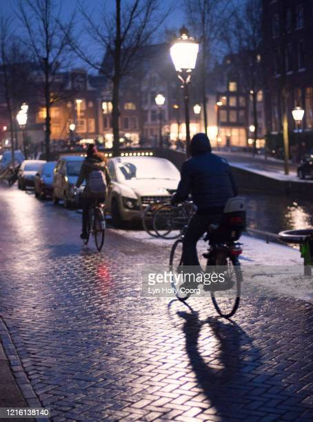 cyclists in amsterdam at night - lyn holly coorg stock pictures, royalty-free photos & images