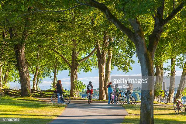 cyclists in park, vancouver - stanley park stock photos and pictures