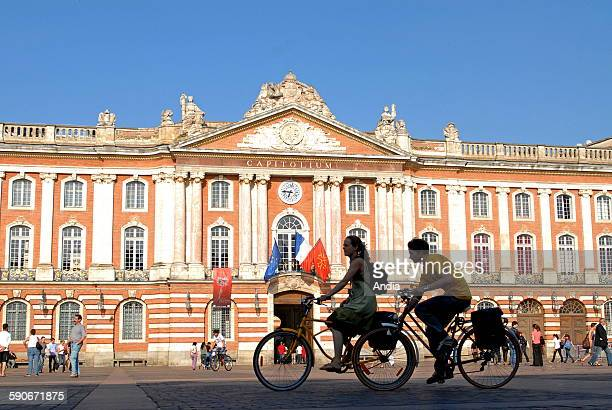 Cyclists in the city teenagers riding bikes and passersby in front of the city hall 'Place du Capitole' square in Toulouse