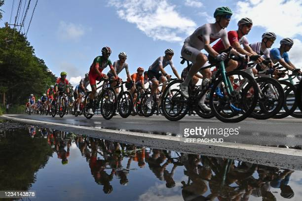 Cyclists in the peloton are reflected on a puddle as they ride past Yamanaka Lake during the men's cycling road race during the Tokyo 2020 Olympic...