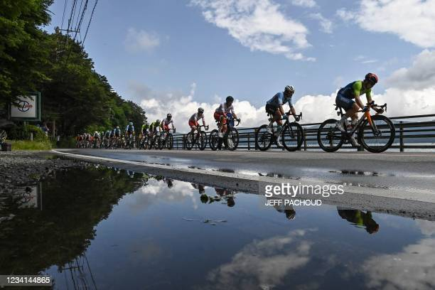 Cyclists in the peloton are reflected on a puddle as they ride past Yamanaka Lake during the men's cycling road race of the Tokyo 2020 Olympic Games...