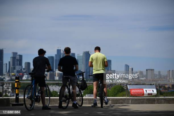 Cyclists look at the view of London city skyline from Greenwich Park south east London on June 2 2020 following a further relaxation of the novel...