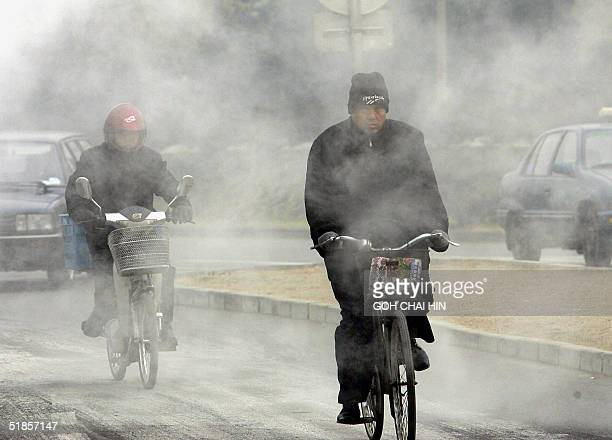 Cyclists make their way along a street in Beijing 14 December 2004 covered in heavy layer of thick smog and pollutants China is now the world's...