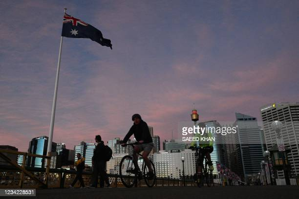 Cyclists make their way on Darling Harbour bridge at sunset in Sydney on July 27 as around half of Australia's 25 million largely unvaccinated...