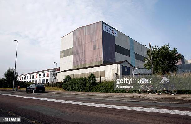 Cyclists make their way past Alstom SA's powergeneration plant in Belfort France on Tuesday June 24 2014 GEs chief executive officer Jeffrey Immelt...