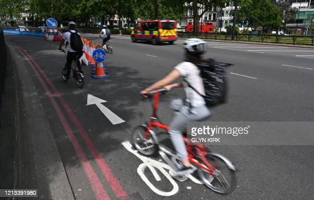 Cyclists make use of a new expanded cycle lane on Park Lane in London on May 17 following an easing of lockdown rules in England during the novel...