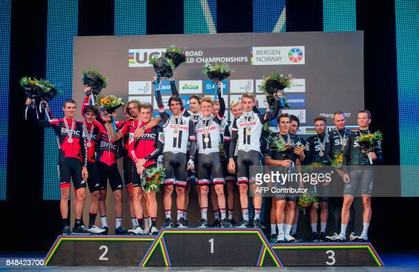 Cyclists of team Sunweb celebrate on the podium next to second place BMC Racing team and third place team Sky after the men's team time trial at the...