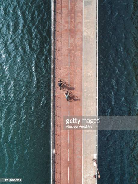 cyclists on a bridge, hong kong - pedestrian walkway stock pictures, royalty-free photos & images