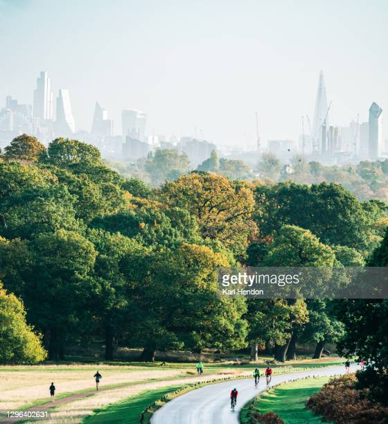 cyclists on a windy road at sunrise in a london park with the city of london in the background - stock photo - richmond upon thames stock pictures, royalty-free photos & images