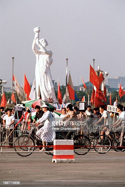 Cyclists on Changan Avenue pass by the 'Goddess of Democracy' as it stands tall amid a huge crowd of flag waving prodemocracy demonstrators in...