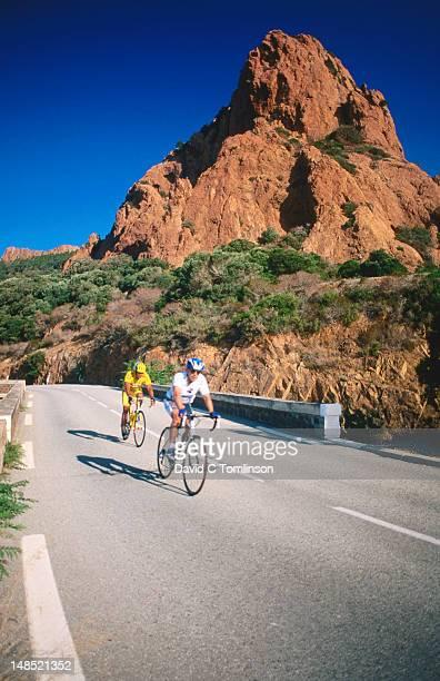 Cyclists on Corniche de l'Esterel with small mountain beyond, near St Raphael, Var.