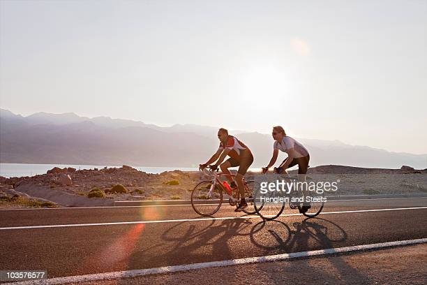 Cyclists on country road by sea