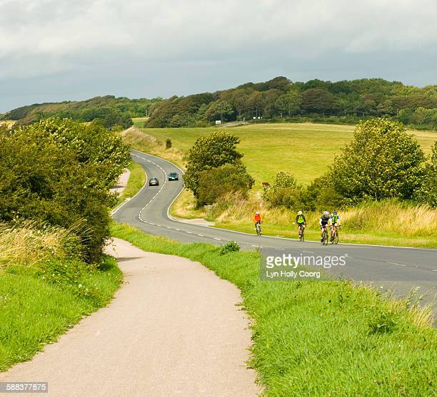 cyclists on countryside road - lyn holly coorg stock pictures, royalty-free photos & images