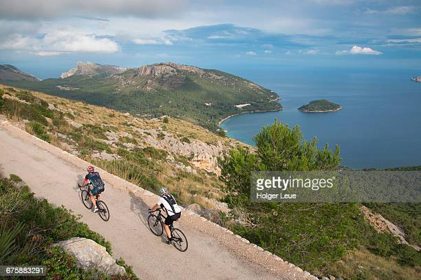 Cyclists on road overlooking Cap de Formentor