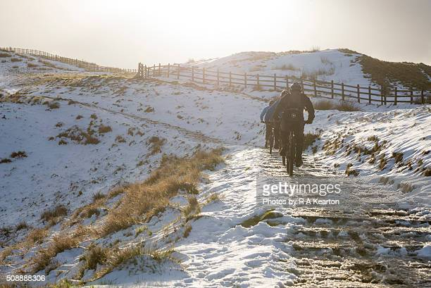 Cyclists on the icy route to the summit of Mam Tor, Derbyshire