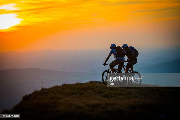 Cyclists on the Top of Mountain at Sunset