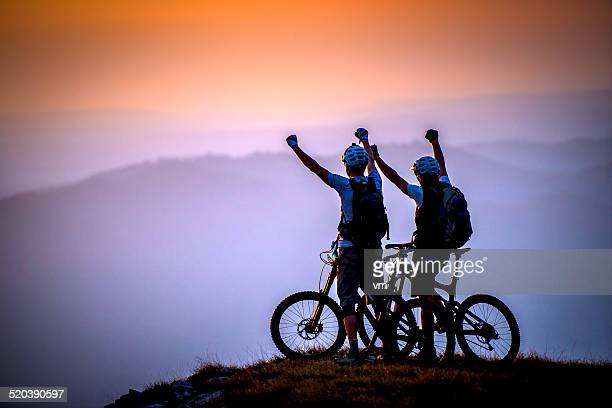 Cyclists on the Top of Mountain Raise Hands at Sunset