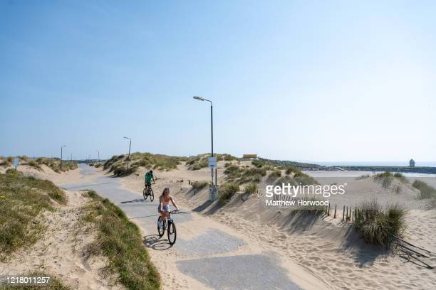 Cyclists on Trecco Bay seafront on April 10 2020 in Porthcawl United Kingdom Police have stepped up patrols to prevent people from travelling to...