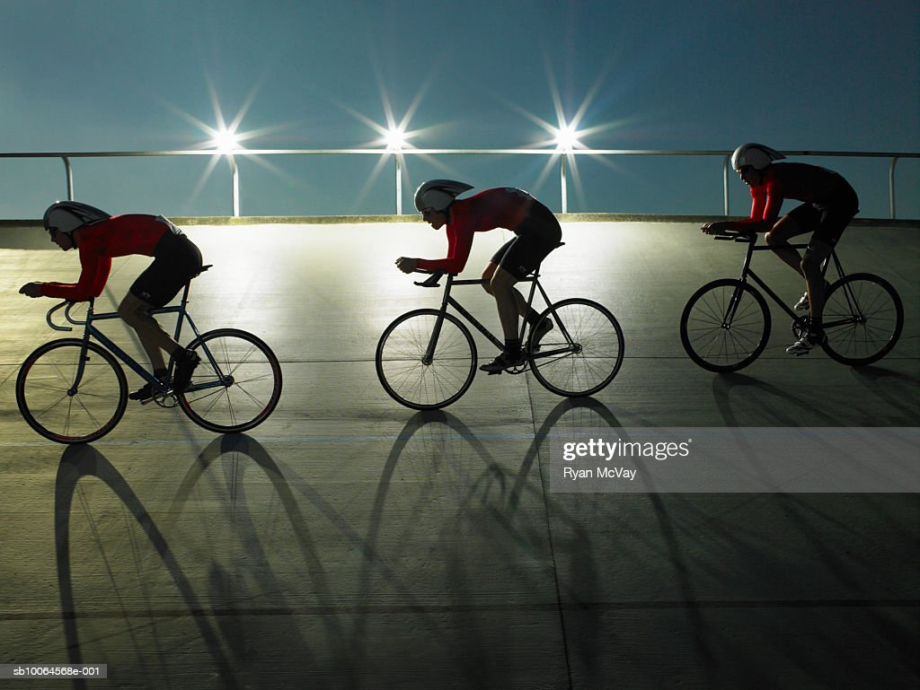 Cyclists on velodrome track at night, side view : Stock Photo