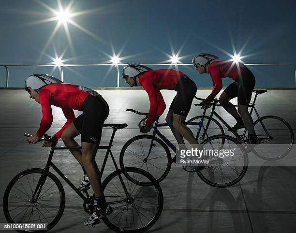 cyclists on velodrome track, side view - track cycling stock pictures, royalty-free photos & images