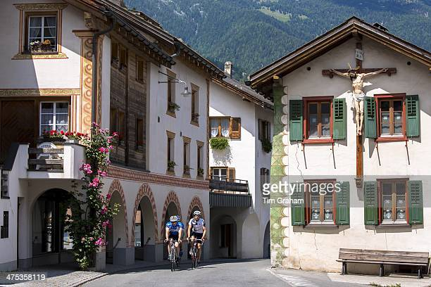 Cyclists pass a crucifix on a traditional house in Mustair Switzerlan