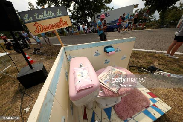 Cyclists pass a fake toilet with a sign that reads 'La Toilette du Dumoulin' during stage 19 of the 2017 Le Tour de France a 2225km stage from Embrun...