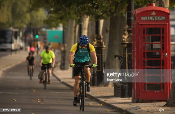 Cyclists pass a red telephone box next to a temporary bike lane in London, U.K. On Monday, Aug. 10, 2020. With a budget of £2 billion over the next...