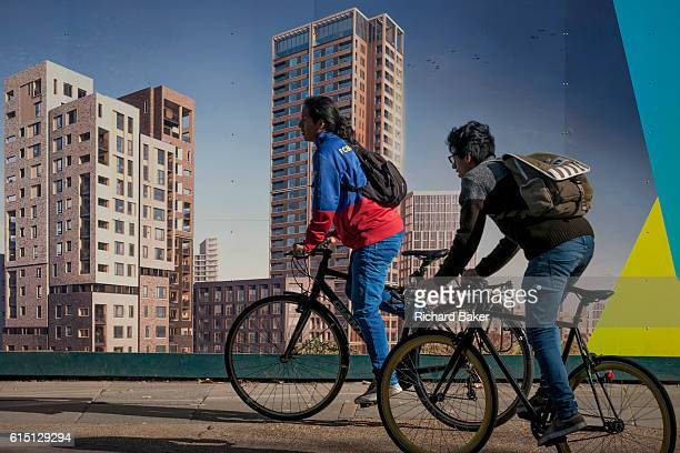 Cyclists pass a regeneration project hoarding at Elephant Park Elephant Castle on 11th October 2016 in London England Southwark Councils development...