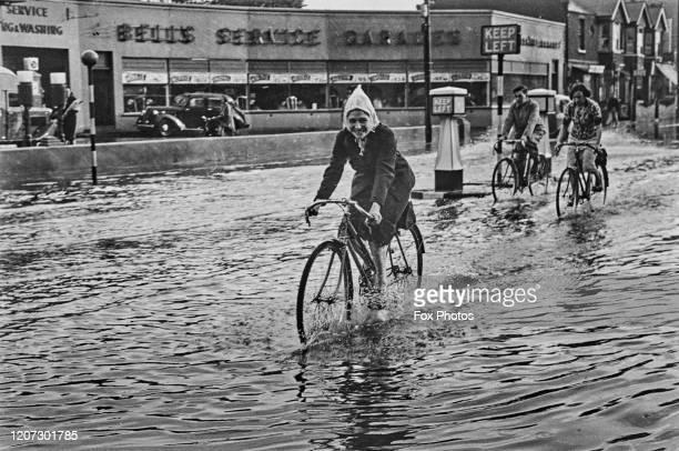 Cyclists pass along flooded roads, United Kingdom, circa 1940.