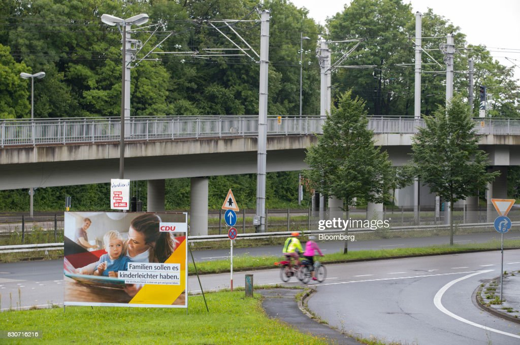 Cyclists pass by a Christian Democratic Union (CDU) election billboard in Dortmund, Germany, on Saturday, Aug. 12, 2017. Angela Merkel, Germany's chancellor and leader of the Christian Democratic Union (CDU), opened her re-election campaign with criticism of the nations auto executives, saying they need to embrace new technology more quickly to protect jobs and repair damage done by adiesel cheating scandal. Photographer: Jasper Juinen/Bloomberg via Getty Images
